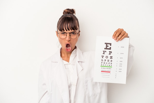 Joven mujer óptica de raza mixta haciendo una prueba aislada sobre fondo blanco gritando muy enojado y agresivo.