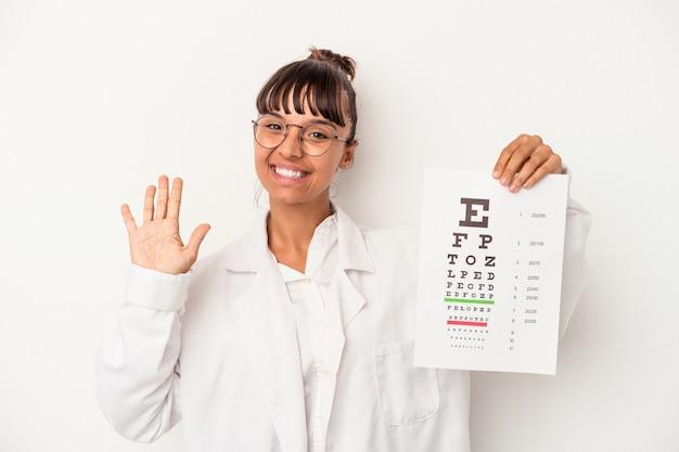 Joven mujer óptica de raza mixta haciendo una prueba aislada sobre fondo blanco sonriendo alegre mostrando el número cinco con los dedos.