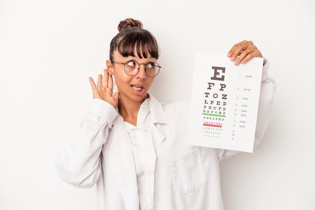 Joven mujer óptica de raza mixta haciendo una prueba aislada sobre fondo blanco tratando de escuchar un chisme.