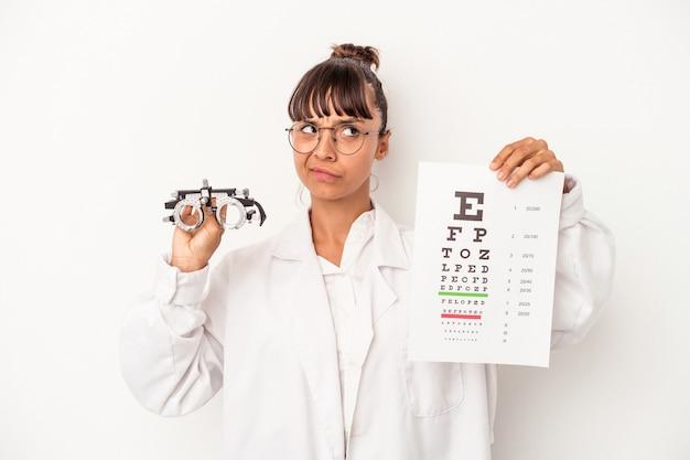 Joven mujer óptica de raza mixta haciendo una prueba aislada sobre fondo blanco.