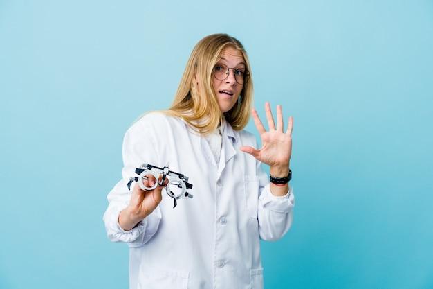 Joven mujer optometrista rusa en azul conmocionada debido a un peligro inminente