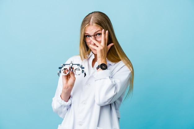 Joven mujer optometrista rusa en azul parpadea a través de los dedos asustada y nerviosa.