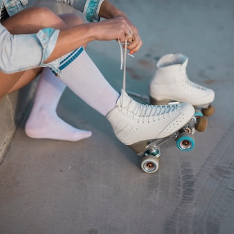 Joven mujer patinadora atando el encaje de patín.