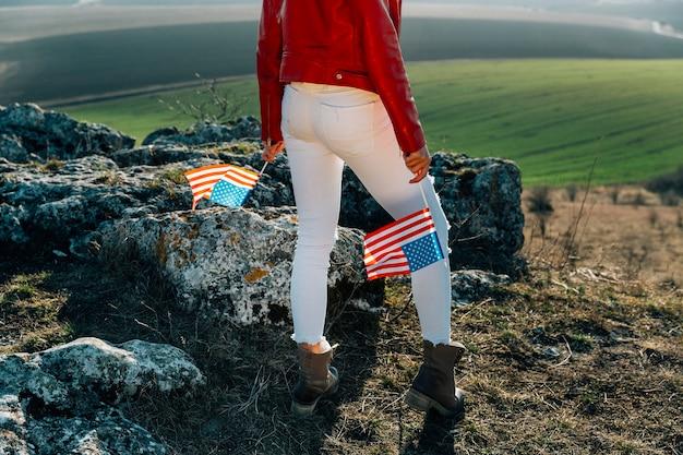Joven mujer patriótica con bandera estadounidense en la cima de la montaña