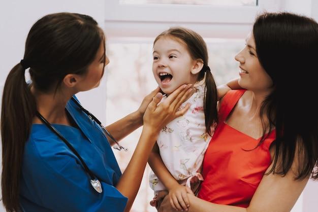 Joven mujer pediatra examinando niños garganta