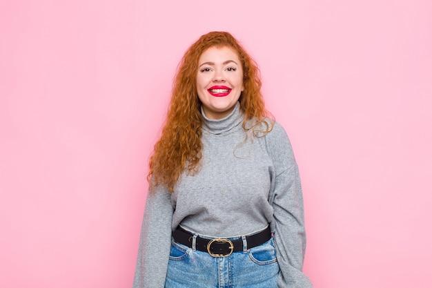 Joven mujer pelirroja que parece feliz y tonta con una sonrisa amplia, divertida y loca y los ojos bien abiertos sobre la pared rosa
