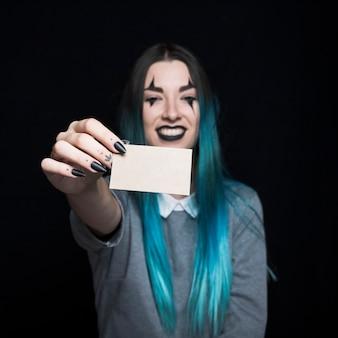 Joven mujer de pelo azul posando con tarjeta de papel