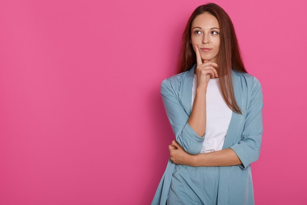 Joven mujer pensando y reflexionando sobre algo con el dedo en la barbilla, mirando a un lado con expresión facial pensativa