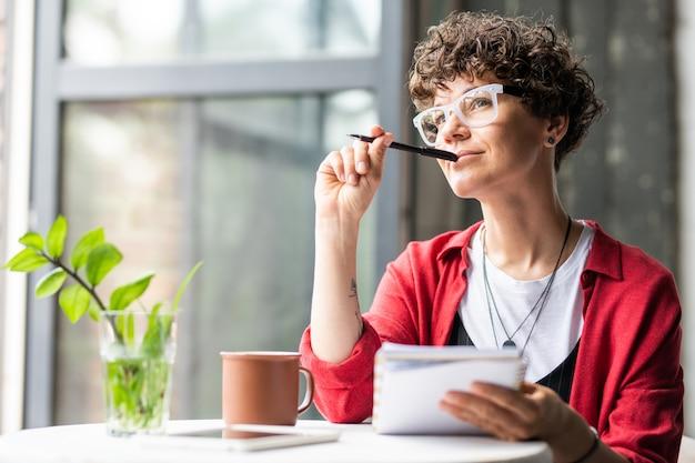 Joven mujer pensativa en anteojos pensando en nuevas ideas creativas mientras está sentado junto a la mesa en la cafetería u oficina