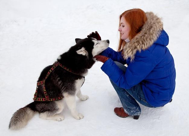 Joven mujer y perro husky siberiano en invierno