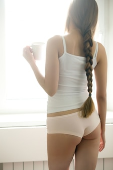 Joven mujer de pie cerca de la ventana de beber café