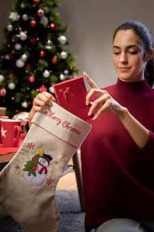 Joven mujer poniendo regalos en medias gigantes