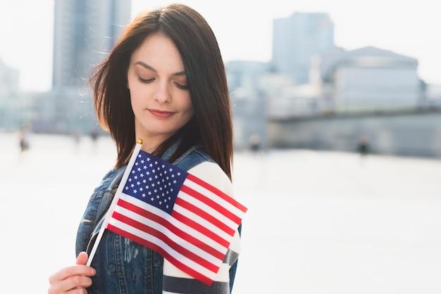 Joven mujer posando con la bandera de estados unidos en el día de la independencia