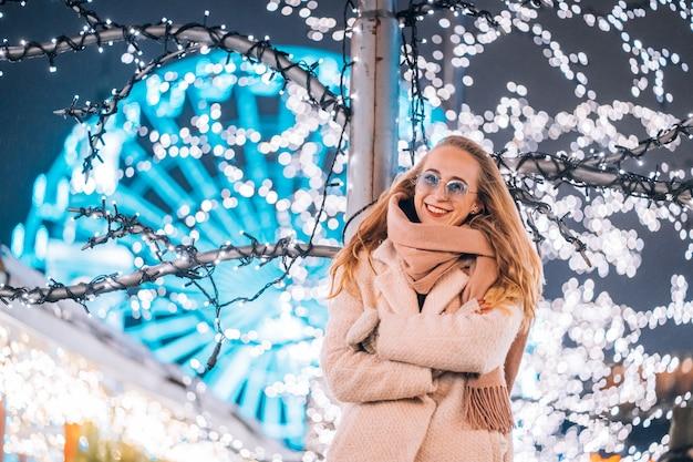 Joven mujer posando en la calle con árboles iluminados