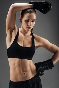 Joven mujer posando con guantes de boxeo