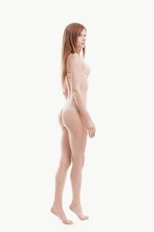 Joven mujer posando en ropa interior, sujetador beige y bragas, piel perfecta