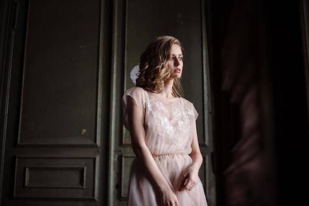 Joven mujer posando en un vestido largo ligero tierno rosa en interiores