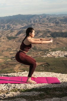 Joven mujer practicando yoga al aire libre