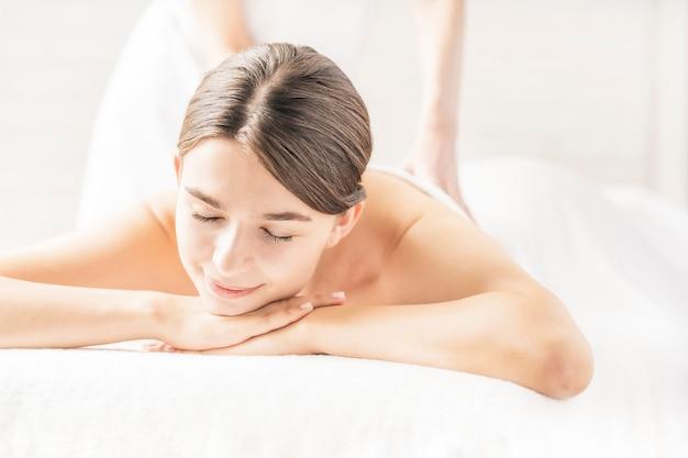 Joven mujer que recibe un masaje en un salón de belleza