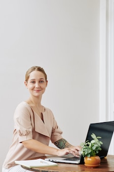 Joven mujer que trabaja en la computadora portátil