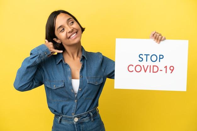 Joven mujer de raza mixta aislada sobre fondo amarillo sosteniendo un cartel con el texto stop covid 19 y haciendo gesto de teléfono
