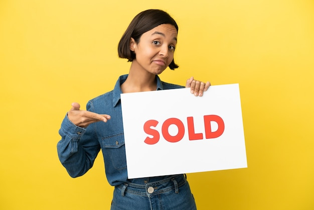 Joven mujer de raza mixta aislada sobre fondo amarillo sosteniendo un cartel con el texto vendido y apuntando