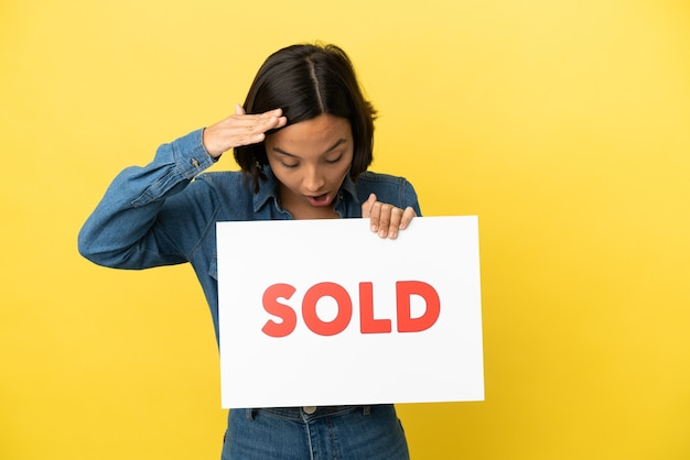 Joven mujer de raza mixta aislada sobre fondo amarillo sosteniendo un cartel con texto vendido con expresión de sorpresa