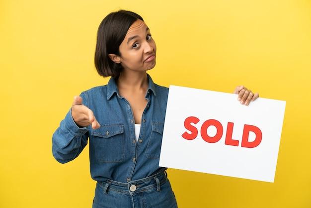 Joven mujer de raza mixta aislada sobre fondo amarillo sosteniendo un cartel con texto vendido haciendo un trato