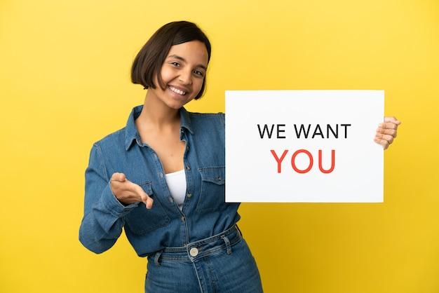 Joven mujer de raza mixta aislada sobre fondo amarillo sosteniendo we want you board haciendo un trato