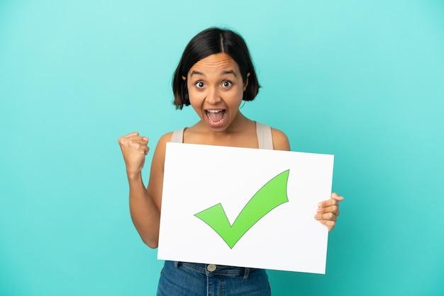 Joven mujer de raza mixta aislada sobre fondo azul sosteniendo un cartel con el icono de marca de verificación verde de texto y celebración de una victoria