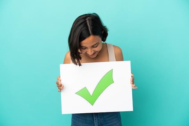 Joven mujer de raza mixta aislada sobre fondo azul sosteniendo un cartel con el icono de marca de verificación verde de texto