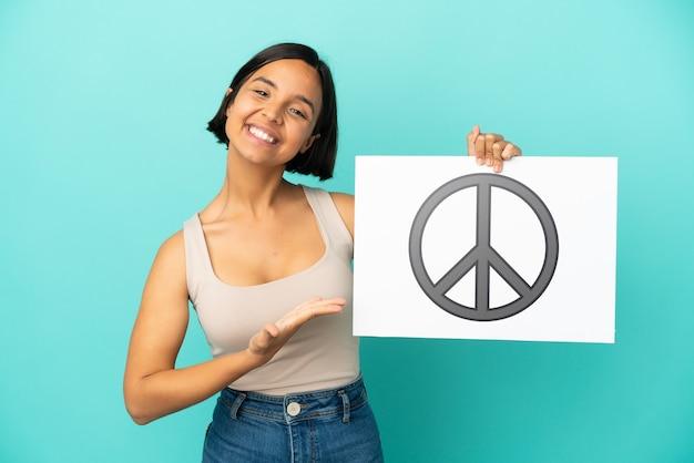 Joven mujer de raza mixta aislada sobre fondo azul sosteniendo un cartel con el símbolo de la paz y apuntando