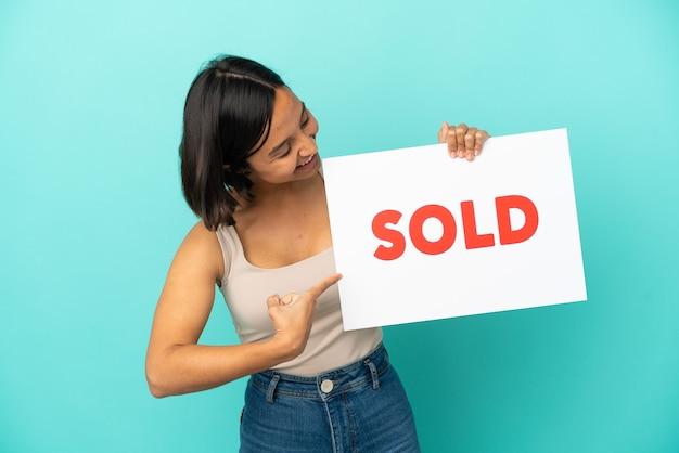 Joven mujer de raza mixta aislada sobre fondo azul sosteniendo un cartel con el texto vendido y apuntando