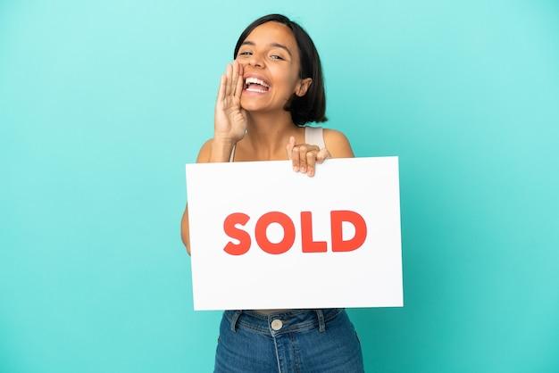 Joven mujer de raza mixta aislada sobre fondo azul sosteniendo un cartel con el texto vendido y gritando