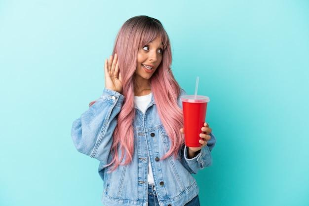 Joven mujer de raza mixta bebiendo una bebida fresca aislada sobre fondo azul escuchando algo poniendo la mano en la oreja