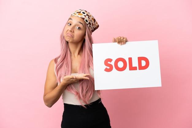 Joven mujer de raza mixta con cabello rosado aislado sobre fondo rosa sosteniendo un cartel con el texto vendido y apuntando