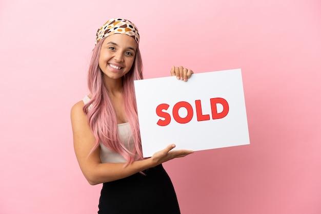 Joven mujer de raza mixta con cabello rosado aislado sobre fondo rosa sosteniendo un cartel con texto vendido con expresión feliz