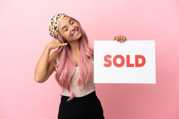 Joven mujer de raza mixta con cabello rosado aislado sobre fondo rosa sosteniendo un cartel con el texto vendido y haciendo el gesto que viene