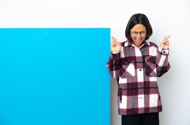 Joven mujer de raza mixta con un gran cartel azul aislado sobre fondo blanco con los dedos cruzados