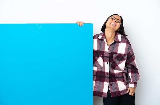 Joven mujer de raza mixta con un gran cartel azul aislado sobre fondo blanco riendo