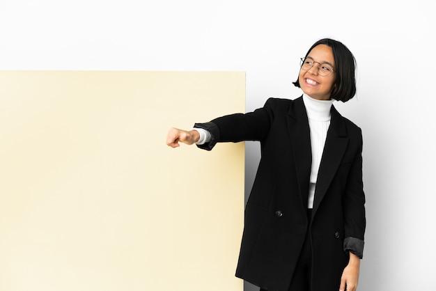 Joven mujer de raza mixta con una gran pancarta sobre fondo aislado dando un gesto de pulgar hacia arriba