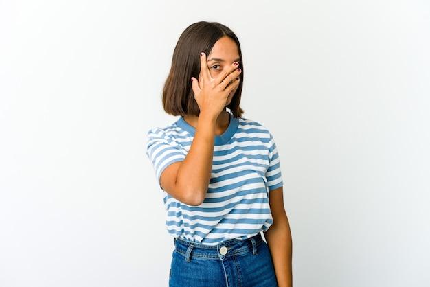 Joven mujer de raza mixta parpadea a la cámara a través de los dedos, avergonzado cubriendo la cara.