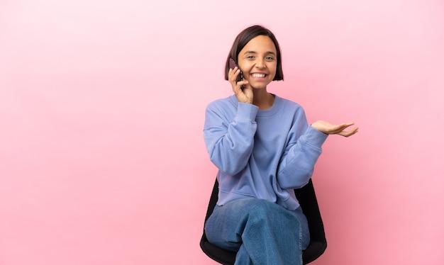 Joven mujer de raza mixta sentada en una silla aislada sobre fondo rosa manteniendo una conversación con el teléfono móvil con alguien