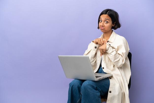 Joven mujer de raza mixta sentada en una silla con portátil aislado sobre fondo púrpura haciendo el gesto de llegar tarde