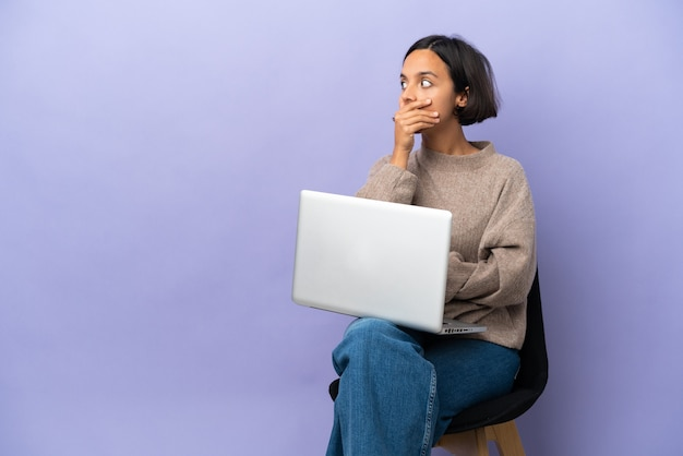 Joven mujer de raza mixta sentada en una silla con portátil aislado sobre fondo púrpura haciendo gesto de sorpresa mientras mira hacia el lado