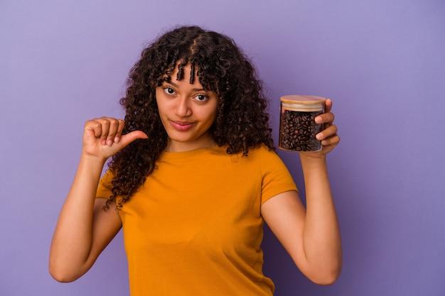 Joven mujer de raza mixta sosteniendo una botella de granos de café aislada sobre fondo púrpura se siente orgullosa y segura de sí misma, ejemplo a seguir.