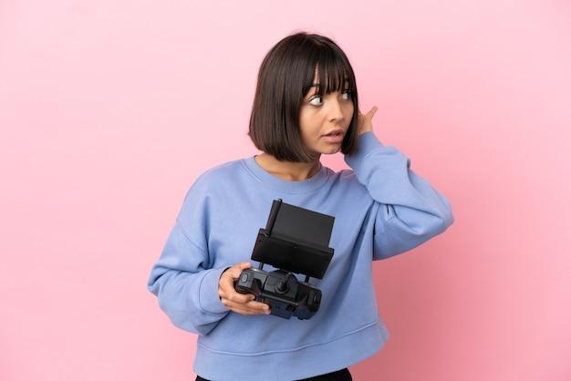 Joven mujer de raza mixta sosteniendo un control remoto de drone aislado sobre fondo rosa escuchando algo poniendo la mano en la oreja
