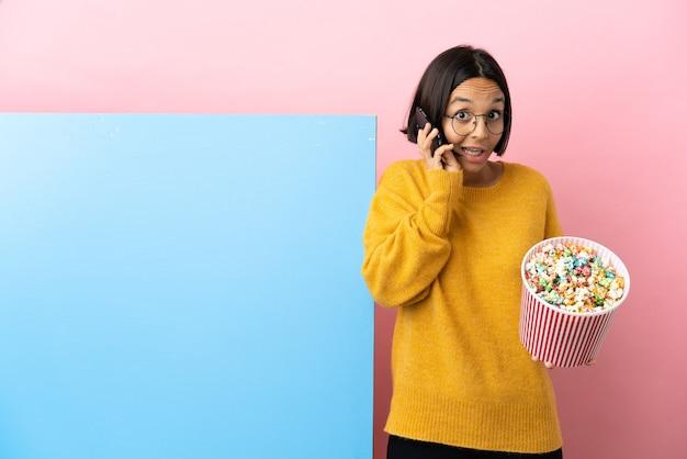 Joven mujer de raza mixta sosteniendo palomitas de maíz con una gran pancarta sobre fondo aislado manteniendo una conversación con el teléfono móvil con alguien