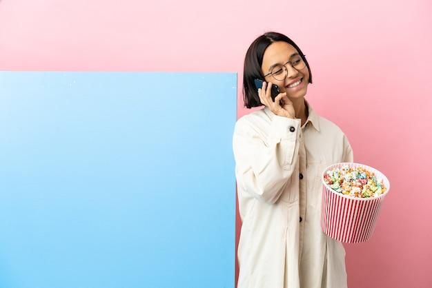 Joven mujer de raza mixta sosteniendo palomitas de maíz con una gran pancarta sobre fondo aislado manteniendo una conversación con el teléfono móvil