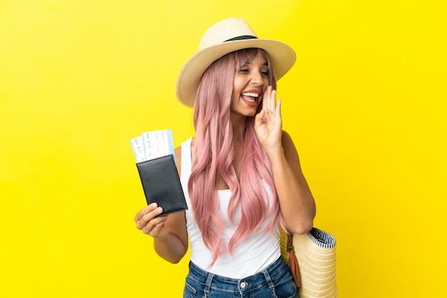 Joven mujer de raza mixta sosteniendo pasaporte y bolsa de playa aislada sobre fondo amarillo gritando con la boca abierta hacia el lado